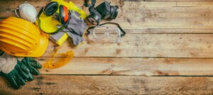 Construction safety. Protective hard hat, headphones, gloves and glasses on wooden background