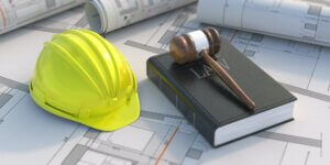 Construction, labor law concept. Judge gavel and book on project blueprint background.